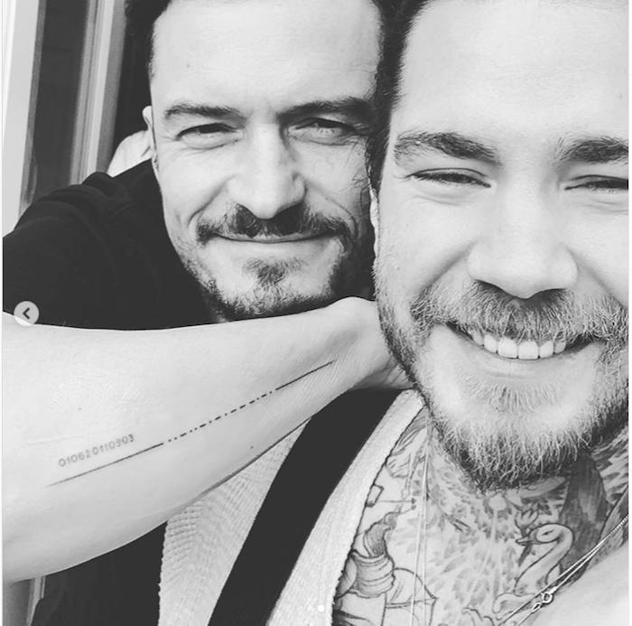 mann mit bart und der schauspiler orlando bloom, eine hand mit einem. tattoo mit morsecode, fehler im tattoo