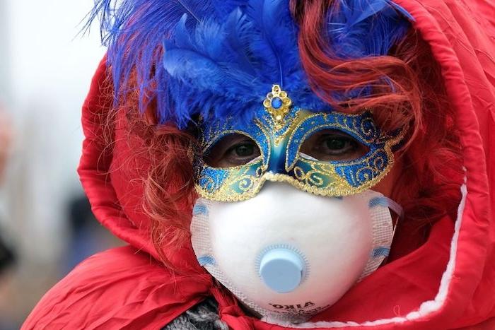 frau mit einer maske mit blauen federn, wegen des neuen coronavirus soll der karneval in venedig abgesagt werden