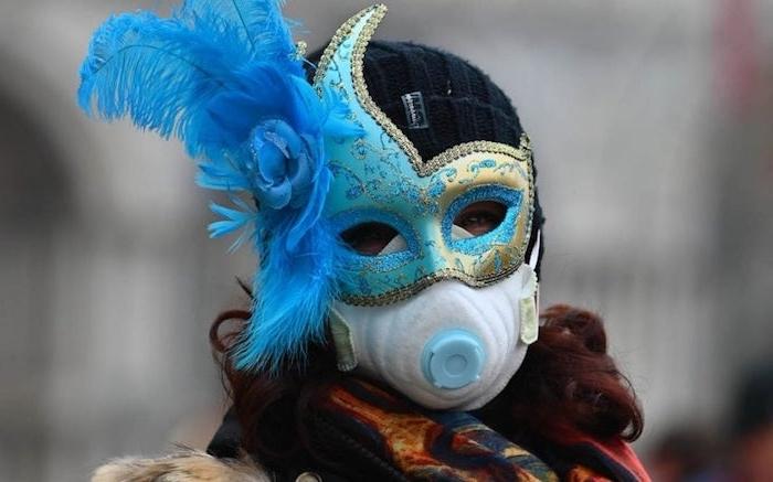 der karneval un venedig, eine frau mit maske mit langen blauen federn, der diesjährige karneval in venedig wird wegen coronavirus beenden
