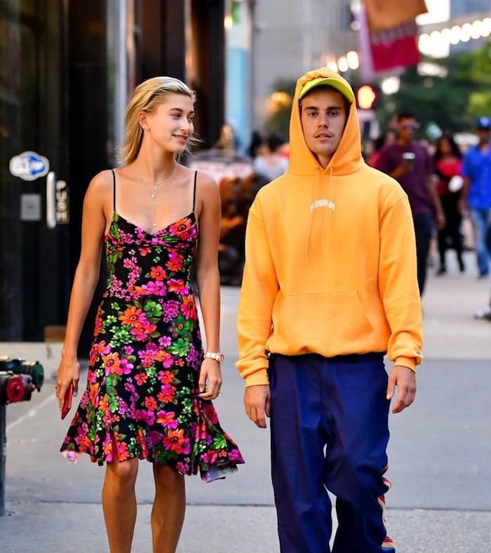 Justin Bieber und seine ehefrau mit einem kleid mit vielen violetten und grünen blumen und einer halskette, eine frau mit blondem haar