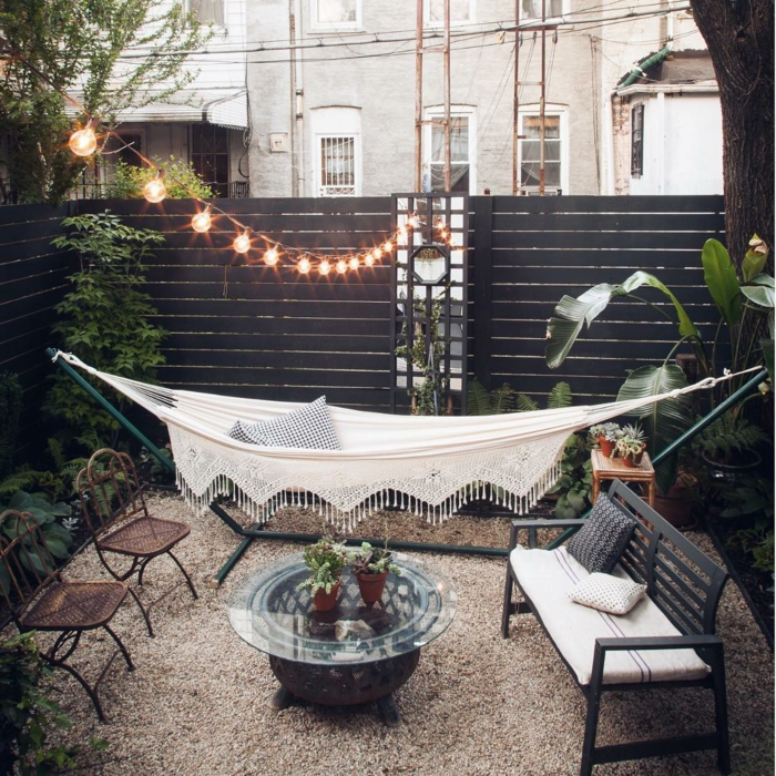 cozy Einrichtung Garten mit weißer Hängematte, Sichschutz aus Holz in braun, aerufgehängte Lichtketten, Boden mit Zierkies, runder Glastisch, gartendeko ideen