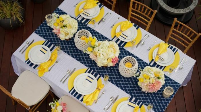 Tischdeko Frühling mit Naturmaterialien, gedeckter Tisch in gelben und blauen Farben und Frühlingsblumen, blauer Tischläufer