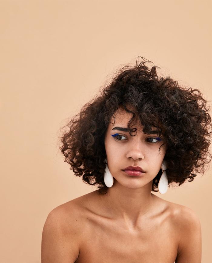 Naturlocken kurz schneiden, Kurzhaarfrisuren für lockiges Haar, Dame mit weißen Ohrringen, dezentes Make-Up