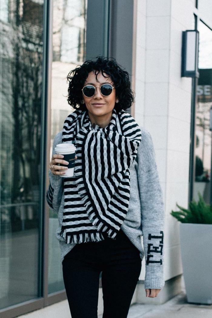 lässiger Style Inspiration, grauer Sweatshirt und schwarze Jeans, lockige schwarze Haare, Kurzhaarfrisuren Damen frech, runde Sonnenbrillen