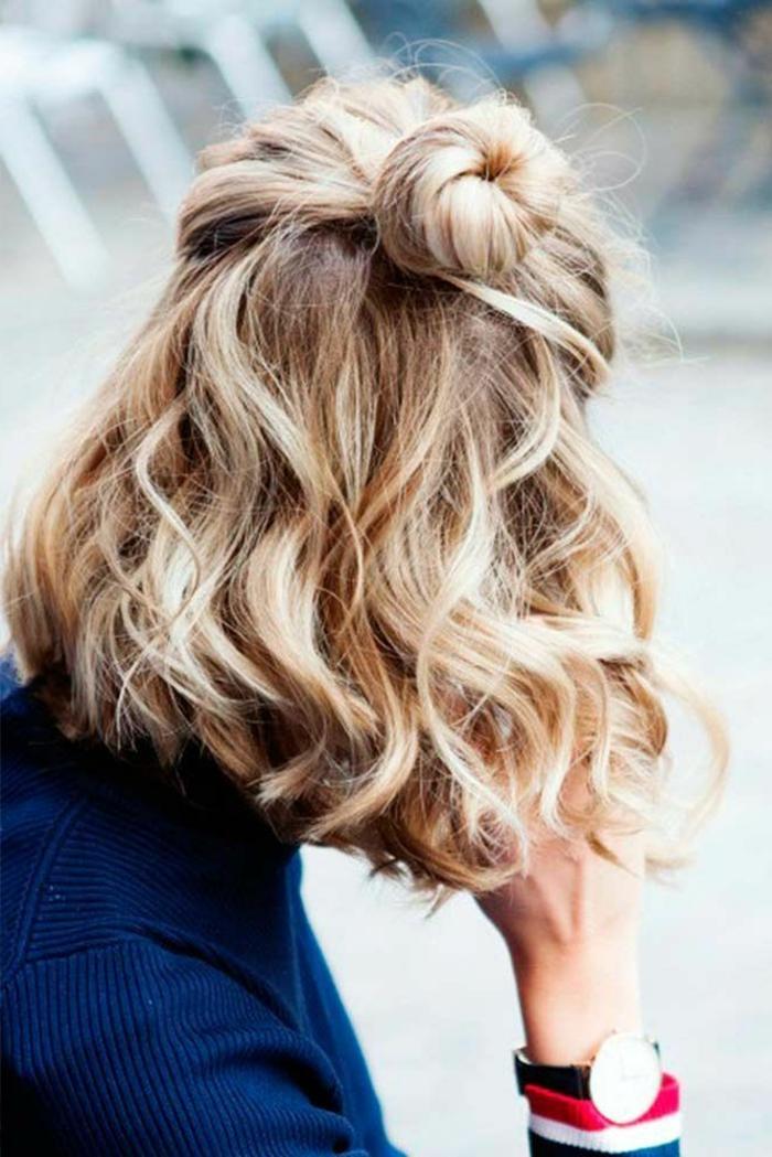 blonde halb hoch halb runter Frisur, Dame angezogen im blauen Sweatshirt, Uhr mit schwarzem Riemen, Frisuren Locken kurz