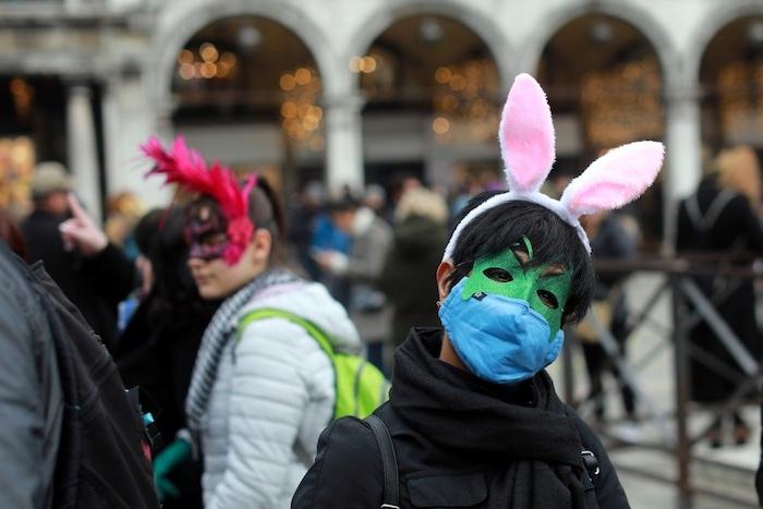 mann mit grüner maske mit langen weißen ohren, wegen coronavirus wird der diesjährige karneval in venedig abgesagt