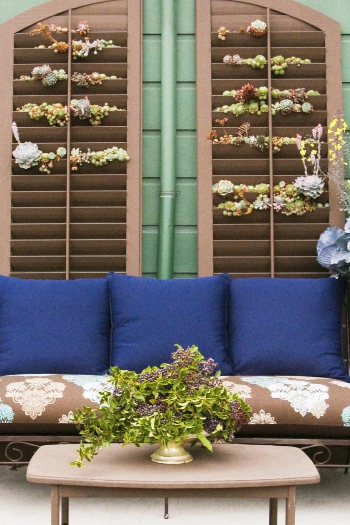 brauner Couch mit grellen blaufarbenen Kissen, Jalousien gefüllt mit Pflanzen, Ideen Gartengestaltung, grüne Pflanze auf einem Tisch