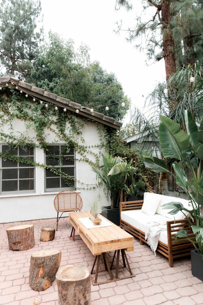 Gartendeko basteln aus Naturmaterialien, Tisch aus Holz, drei Stümpfe als Stühle, Dekoration aus grünen Pflanzen,