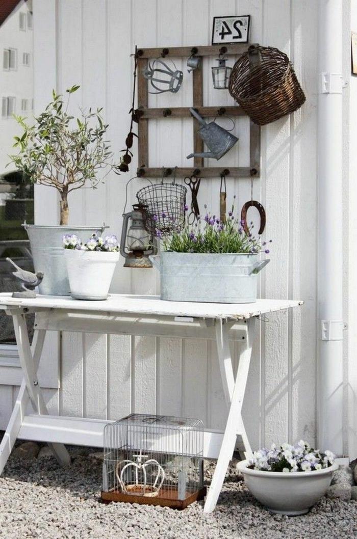 Ecke für Gartenzubehör mit einem recycletem Tisch in weiß, Boden aus Zierkies, Töpfe mit Blumen und einem kleinen Baum, Gartendeko aus Holz