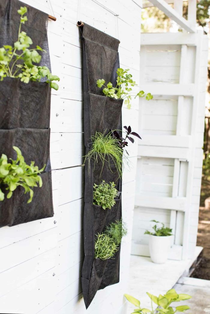 Vertikaler Kräutergarden für einen kleine Raum aus schwarzem Stoff, aufgehängt an weiße Wand, Deko für Garten und Terrasse