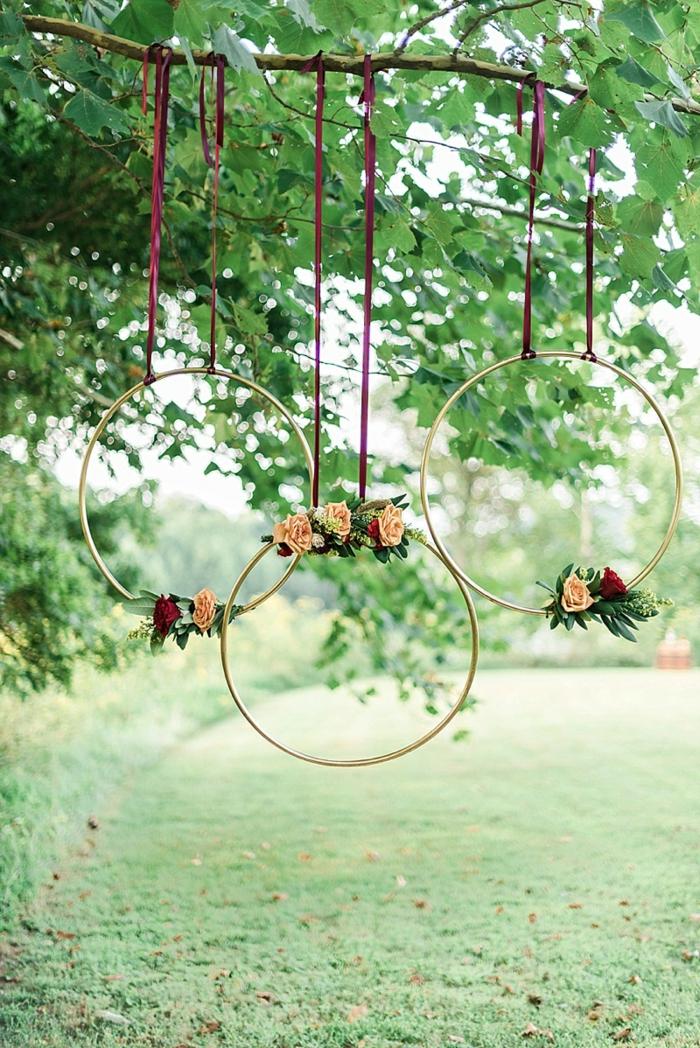 drei große Ringe aufgehängt auf einem Baumzweig und dekoriert mit rosa und rote Rosen, Gartendeko selber machen