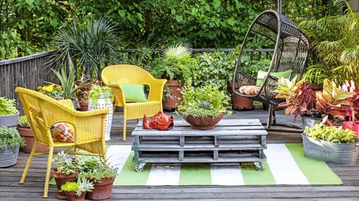 Einrichtung eines Gartens in hellen Farben, zwei Stühle in gelb, Teppich in weiß und grün, viele grüne Pflanzen, ideen Gartengestaltung