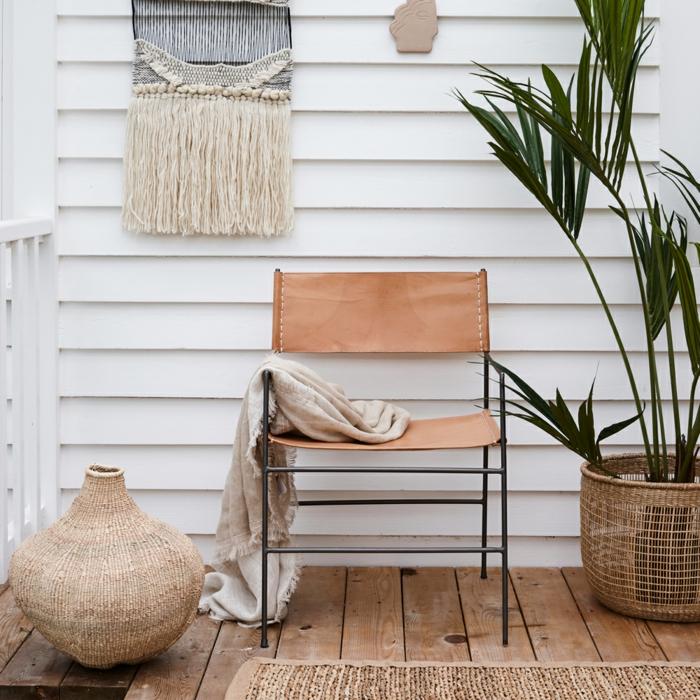 Terrasse in einem Garten mit Lederstuhl, Boden aus Holz, weiße Wand mit augehängter Dekoration, große grüne Pflanze, Deko für Garten und Terrasse