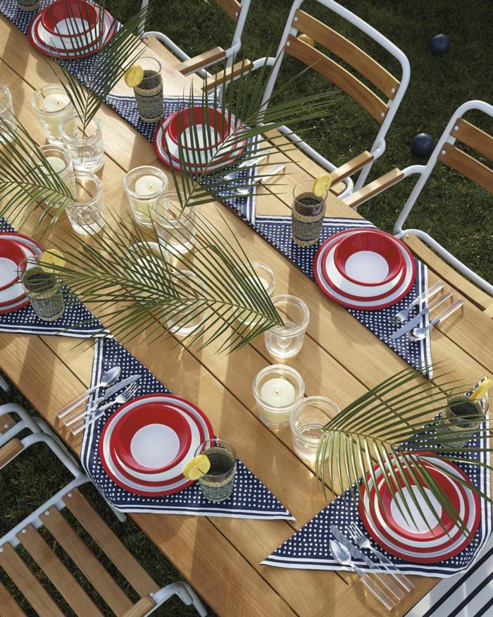 Festlich gedeckter Gartentisch für eine Party, rot weiße Teller und Schalen, blaue Servietten mit weißen Pünktchen, Palmzweige als Dekoration, Gartendeko Ideen