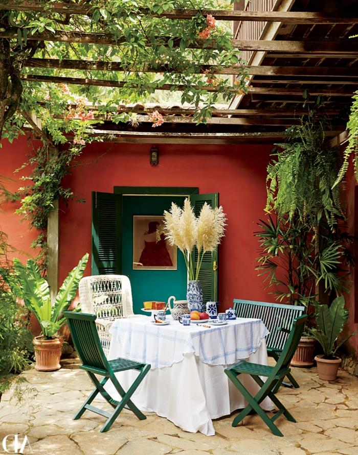 idyllische Gestaltung eines Gartens mit einem kleinen Esstisch und grünen Stühlen, Wände in orange Farbe, pinterest Garten