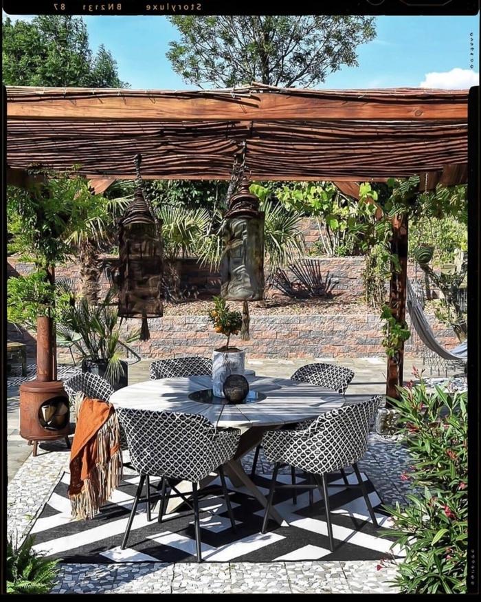 Garten eingerichtet mit Pergola, runder Esstisch mit vier schwarz weißen Stühlen und Teppich, viele grüne Pflanzen, Gartengestaltung Ideen Bilder
