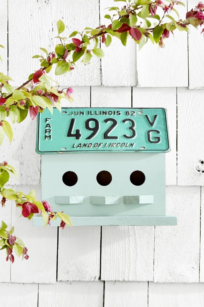 DIY Idee für Vogelhaus mit Nummernschild in grün, Garten Ideen selber machen, weiß bemalte Wand, Baum mit grünen und roten Blättern
