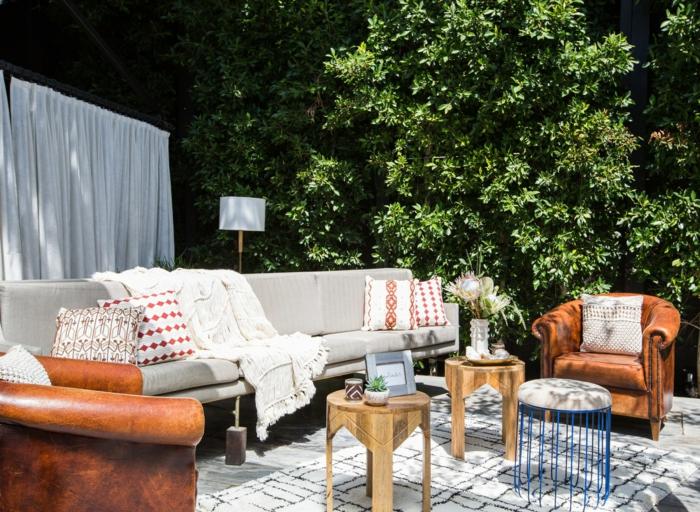 modische Einrichtung eines Gartens, großer grauer Couch, Sessel in Ziegelrot, weißer Teppich mit schwarzen Strichen, Gartengestaltung Ideen