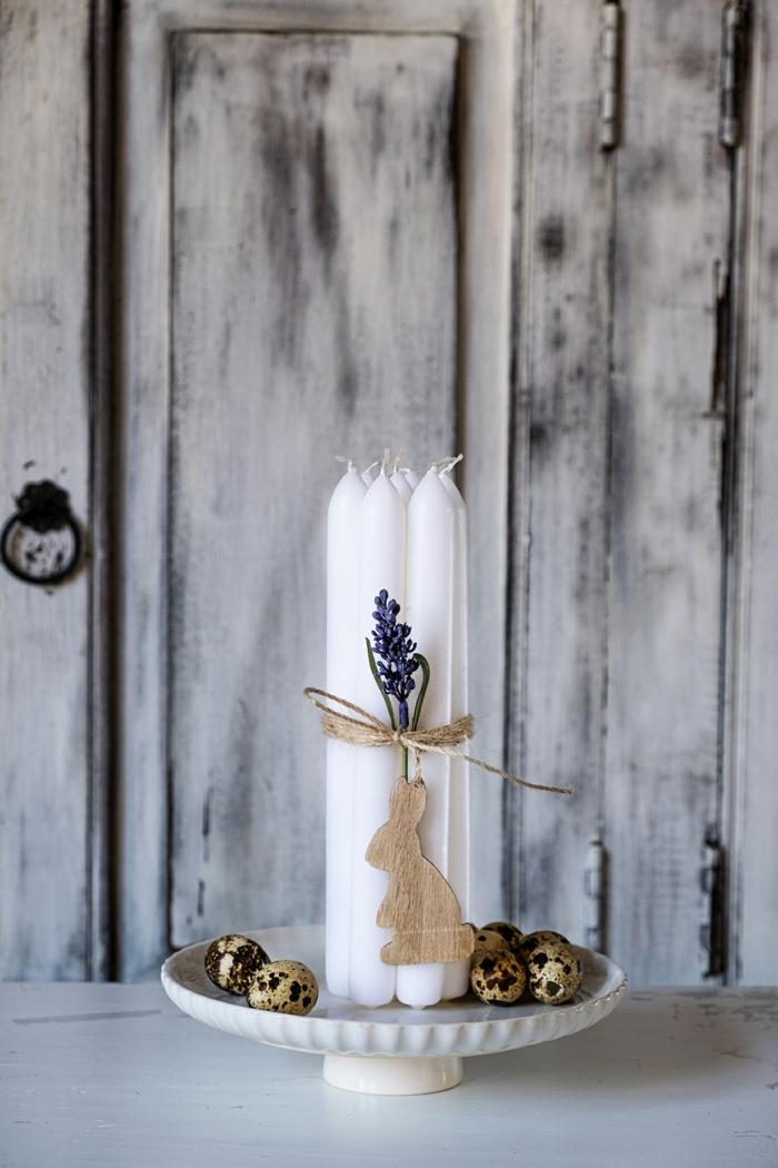 große weiße Kerze auf einem Kuchenteller, umwickelt mit einem Band mit einem hängenden Hasen aus Holz. Osterdeko Holz