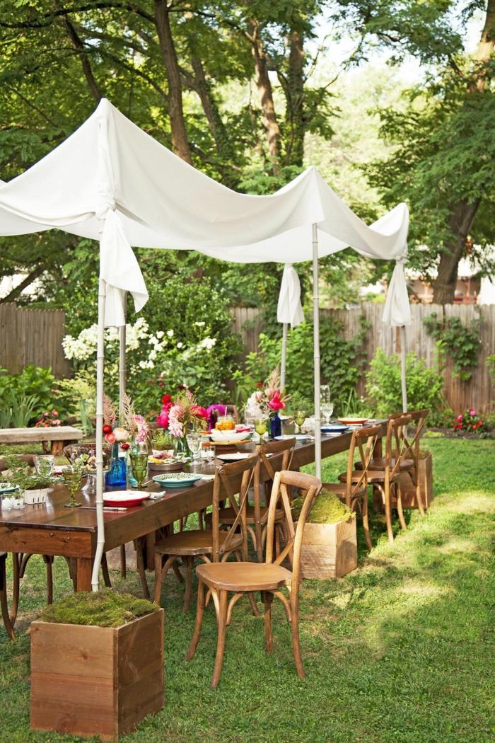 Garten eingerichtet für eine Party mit langem Tisch und weißer Sichtschutz, bunte Blume auf den Tisch, Gartengestaltung Ideen Bilder