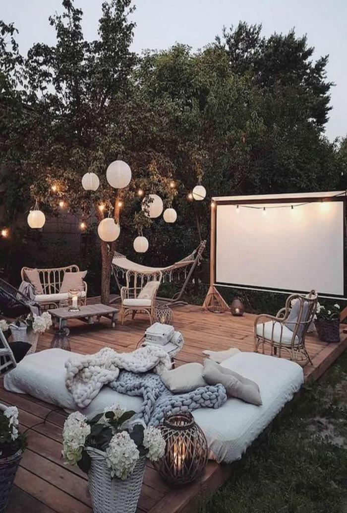 Cozy Einrichtung vom Garten mit großem Bildschirm, kleine und große Kissen, hängende Lampen, ideen Gartengestaltung