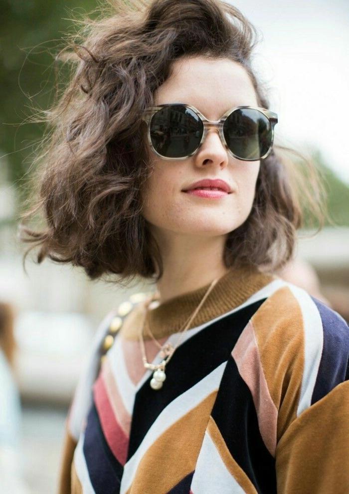 Nahaufnahme einer eleganten Dame, Kurze Frisuren Frauen mit weichen Locken, runde Sonnenbrillen, bunte geometrische Bluse