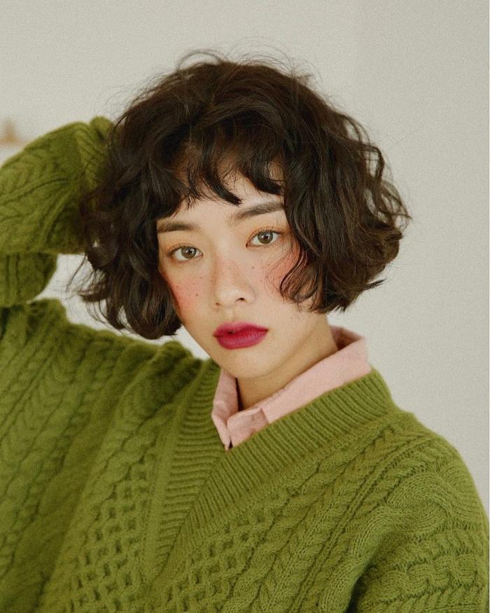 kurze Frisuren mit Locken, Bob Haarschnitt, Dame angezogen im grünen weiten Pullover, leicht geschminktes Gesicht mit Rouge und Lippenstift