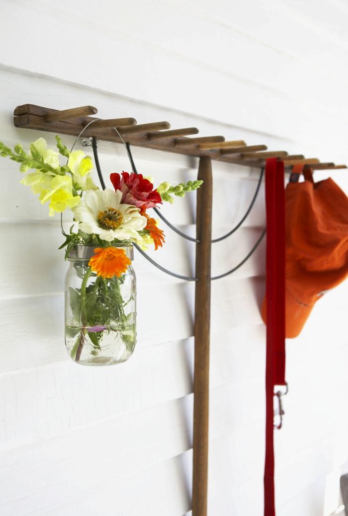 Rechen aus Holz aufgehängt an weiße Wand, Upcucletes Eimachglas mit bunten Blumen auf das Rechen, rote Mütze, Gartendeko aus Holz,