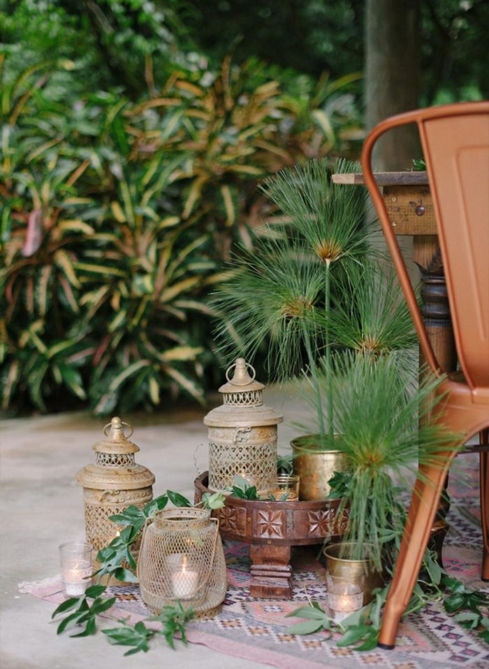 Laternen und Kerzenhalter auf einem bunten Teppich im Garten, Gartengestaltung Ideen, brauner Stuhl