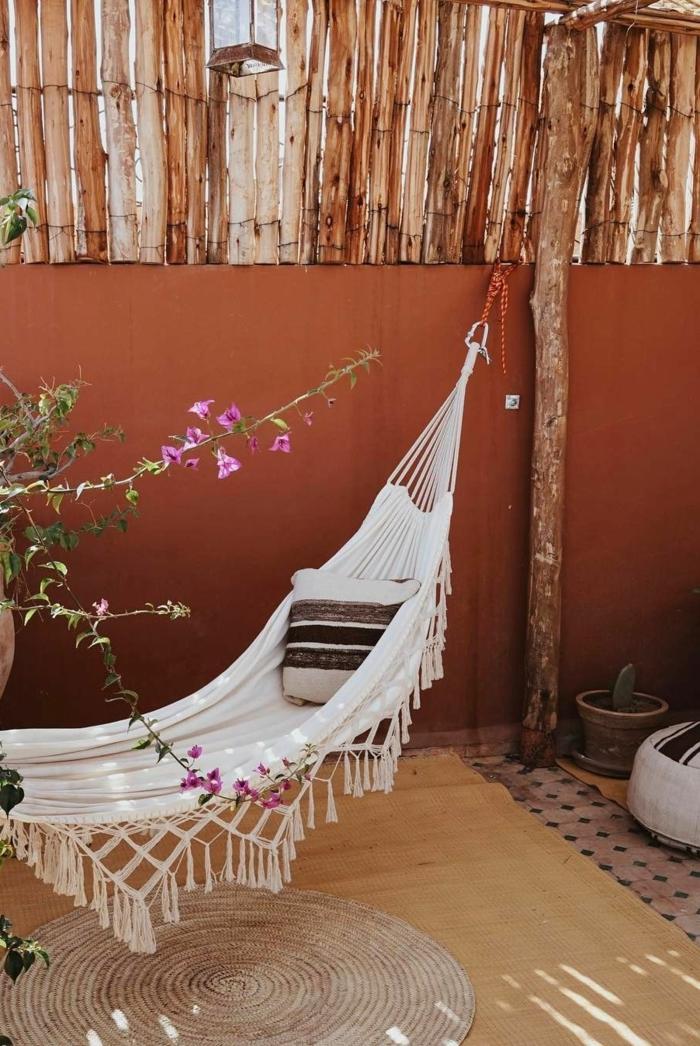 Deko für Garten und Terrasse, Gemütliche Einrichtung eines Gartens mit Hängematte in weiß mit einem Kissen drin, ziegelfarbene Wand, runder Teppich, deko ideen Garten