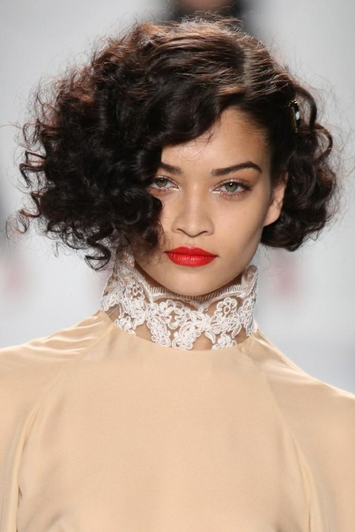 Laufsteg Foto eines Models, beiges Kleid mit Kragen aus Spitze, kurze Frisuren mit Locken, roter Lippenstift
