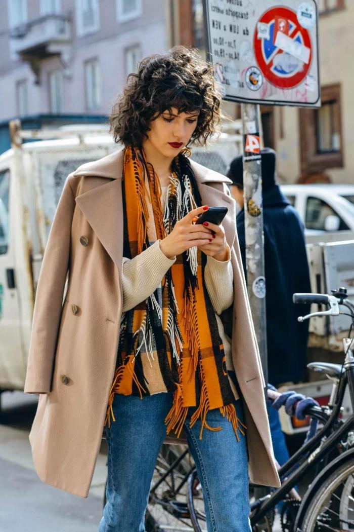 Streetstyle Fotografie, modern angezogene Frau mit hellbraunem Mantel und orangem Schal, kurze Haare Locken, Frau guckt auf ihr Handy