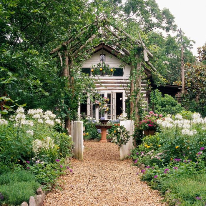 idyllisches Haus mit schönem grünen Garten, kleine Gartentür in weiß, Gartendeko aus Holz, Boden mit Zierkies