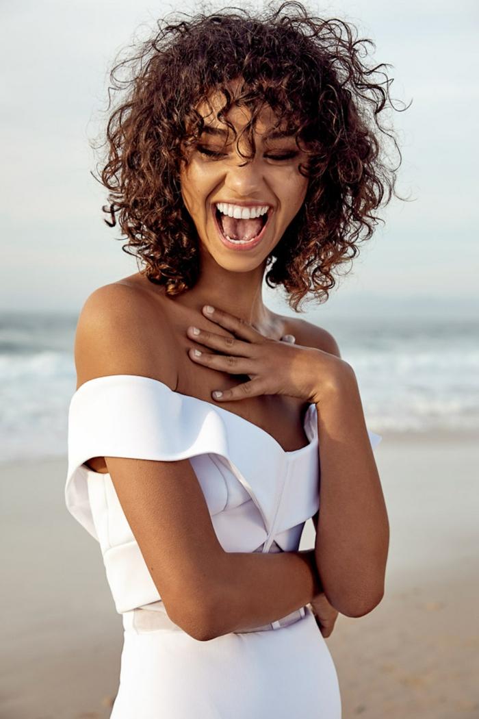 Fotoshooting am Strand, lächelndes Model angezogen im weißen Kleid, Naturlocken Frisuren kurze Haare
