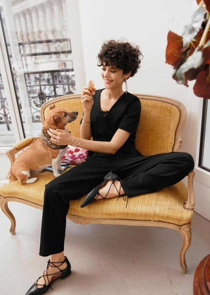 Frau im schwarzen Outfit sitzt in einem gelben Sessel mit einem kleinen Hund, dunkle Kurzhaarfrisuren Locken, schwarze Schuhe mit Schnürsenkel,