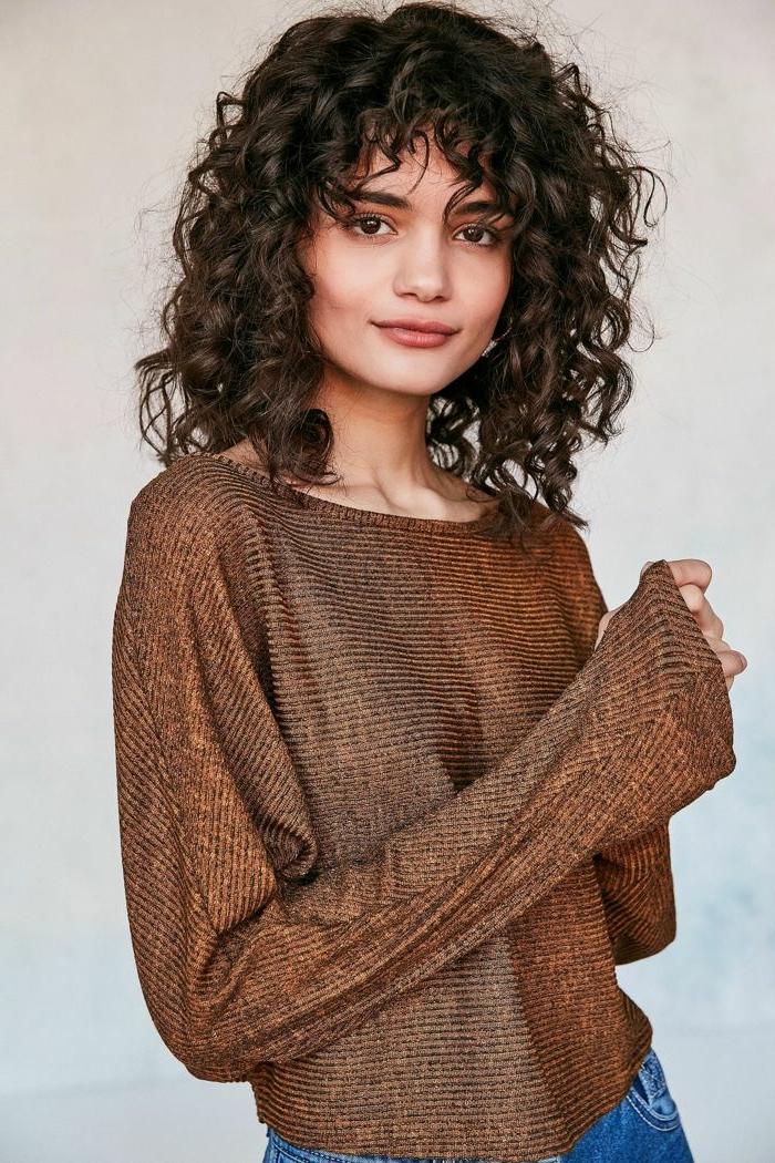 Kurzer Haarschnitt mit Locken, Naturlocken Frisuren, dunklebrauner weiter Pullover und Jeans, dezentes Make-Up