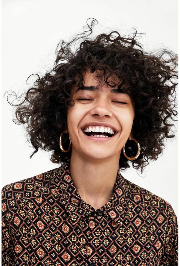 Nahaufnahme einer lächelnden Frau mit lockigen Haaren, modische Kurzhaarfrisuren, kleine Kreolen, buntes Hemd