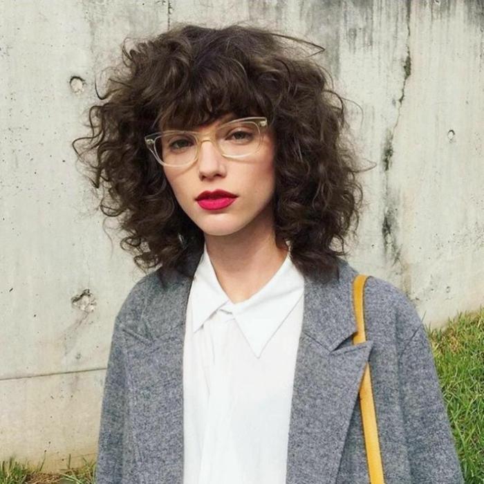 Artsy Fashion Style, Dame mit kurzen lockigen Haaren, weißes Hemd mit Kragen, grauer Mantel, kurze Haare Locken, gelbe Tasche