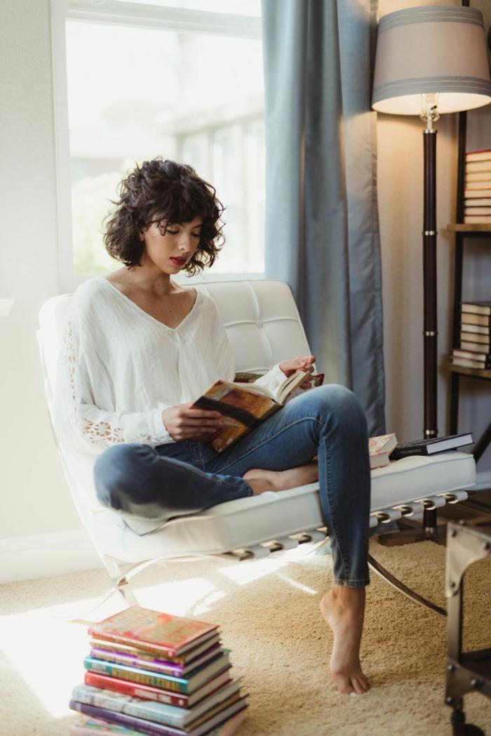 Frau sitzt im weißen Stuhl und liest ein Buh, angezogen in Jeans und weißer Bluse, kurze dunkle Haare, Kurzhaarfrisuren Locken