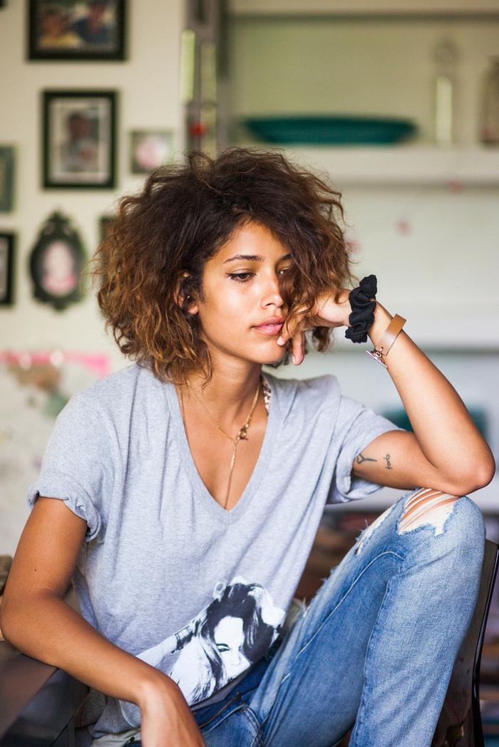 Bequem angezogene Frau in gerippten Jeans und weites graues T-Shirt, Kurzhaarfrisuren für lockiges Haar, Frisuren Locken kurz,