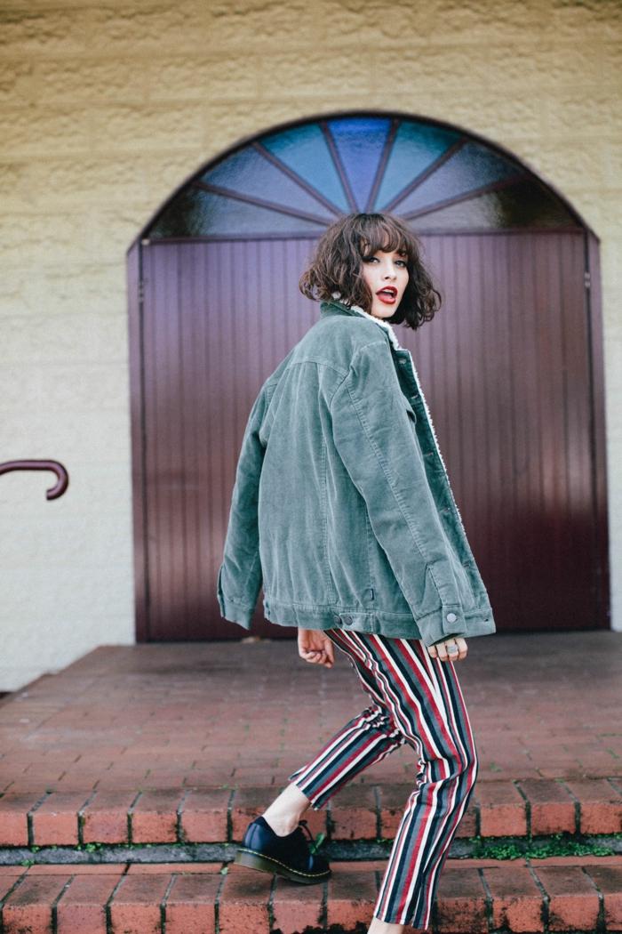 Modernes Outfit mit bunten rot weiß schwarz gestreiften Hosen und weiter Jacke, Kurzhaarfrisuren Frauen frech mit Pony, Oxford Schuhe