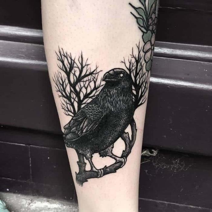 männer tattoo arm, schwarzer vogel am zweig, tätowierung mit rabe als motiv