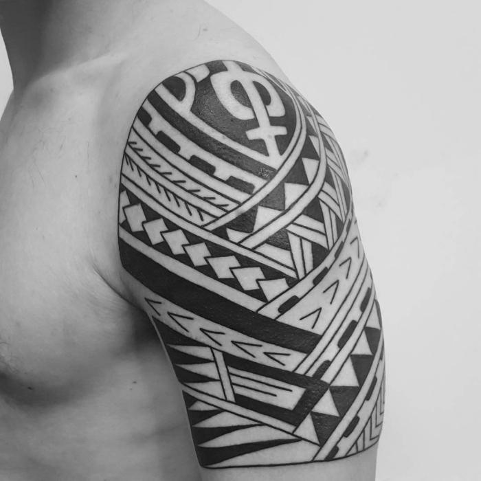 männer tattoos motive, mann mit blaackwork tätowierung an der schulter, maori elemente