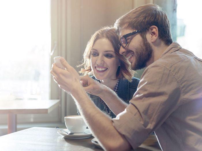 die besten apps für paare, ein mann mit bart und brille und eine junge frau, tisch aus holz