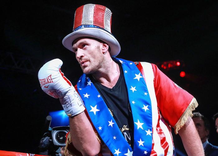 junger mann mit einer großen britischen fahne, der boxer tyson fury, ein mann mit großen weißen boxhandschuhen