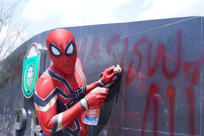 ein mann mit einem kostäum von dem superhelden spiderman, rudi hartono räumt den müll auf