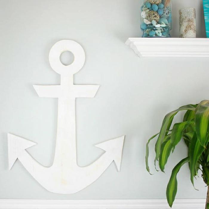 DIY Anleitung für maritime Wandgestaltung, große Anker aus Holz bemalt in weiß, große grüne Pflanze daneben
