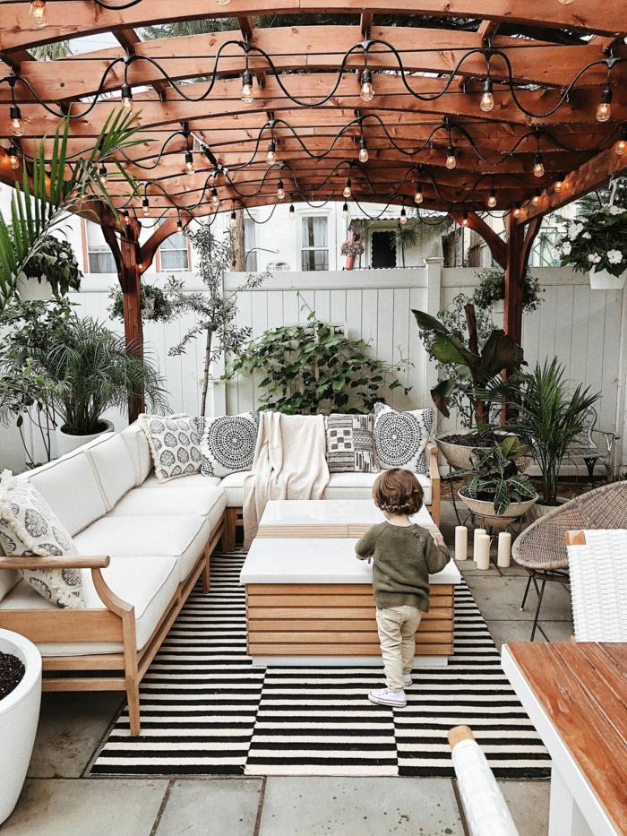 modische Einrichtung eines Garten mit Motiven aus Holz, aufgehängte Lichtketten, Ecksofa mit weißem Kissen, schwarz weißer Teppich, Ideen Gartengestaltung