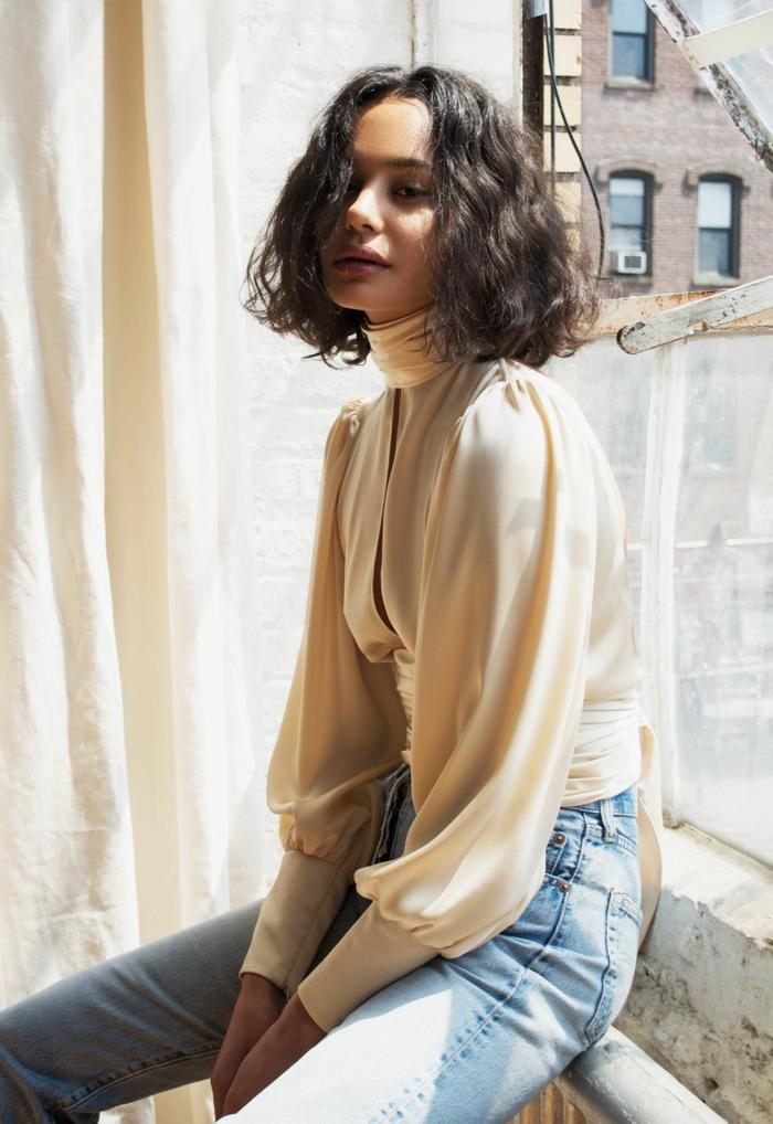 Lässig angezogen Frau sitzt an einem Fenster,weiße Rollkragenbluse und Jena, Haarschnitt Locken, Kurzhaarfrisuren für lockiges Haar.