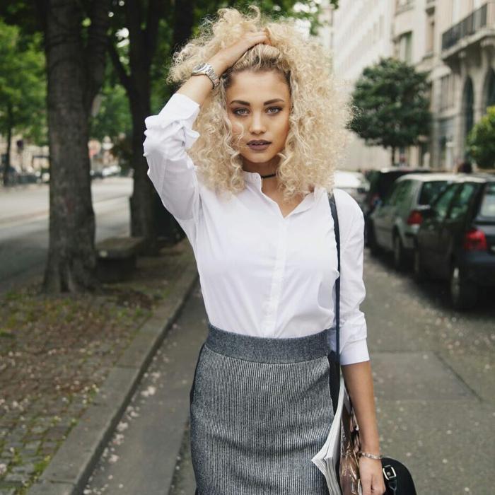 Foto auf der Straße, elegante Blonde Frau angezogen im grauen Rock und weißes Hemd, Kurzhaarfrisuren Locken, blonde Haare, schwarze Minitasche
